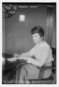 Margaret Sanger, 1914, seated at a desk with pen and paper